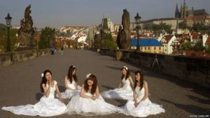 Newly married brides wait for their photo to be taken on the landmark Charles Bridge in Prague