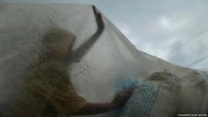 A Palestinian worker uses a plastic sheet to cover sacks of flour from the rain