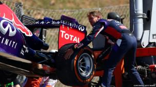 Sebastian Vettel of Germany and Infiniti Red Bull Racing helps to load his car onto a truck after breaking down