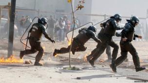 A Chilean riot police officer trips and falls down as he and his fellow officers run away from a petrol bomb thrown by protesters in violent clashes