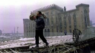 Man carrying firewood outside library, 1994
