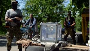 Pro-Russian fighters guard a ballot box during an independence referendum at their position in the eastern Ukranian city of Slavyansk on May 11, 2014