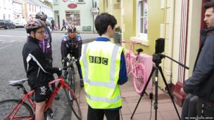 Amateur Cyclists and School Reporter with cameraman in front of a house