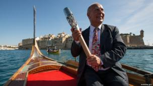 Man in gondola posing with Queen's Baton.