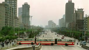 Two city buses block Jianguomen Avenue, the main street to Tiananmen Square, on 21 May 1989