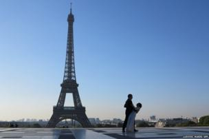 A couple stand in front of the Eiffel Tower in Paris, France