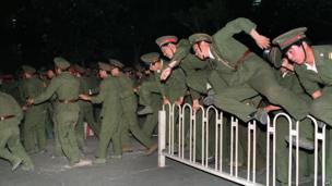 People Liberation Army soldiers leap over a barrier at Tiananmen Square in central Beijing on 4 June 1989