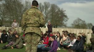 Serving soldier speaks to group of students in World War One cemetery