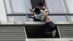 A police officer grabs a man who tried to jump off the seventh floor of a hotel