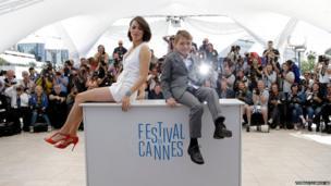 Actors Berenice Bejo andAbdul Khalim Mamatsueiv pose
