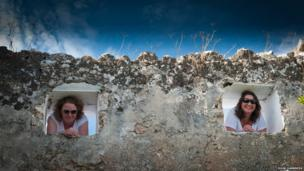 Portrait of two women looking through a wall