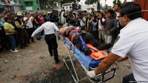 Paramedics move an injured officer into a police ambulance