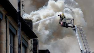 Smoke could be seen billowing from the roof of the building and flames coming from some windows on the upper floors.