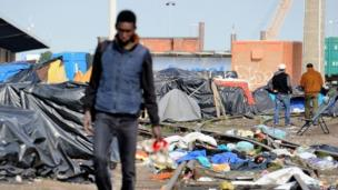 A man walks through a makeshift camp set up by migrants in Calais