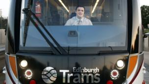 Craig Scotland drives the first tram carrying paying passengers at the Gyle shopping centre in Edinburgh.
