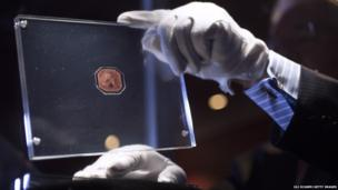 An employee of Sotheby's auction house in London olds a case containing the sole-surviving British Guiana One-Cent Magenta stamp