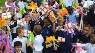 Schoolchildren waving flags in Sunset Park, Birmingham