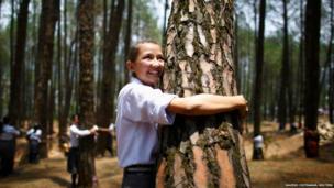 In Kathmandu a girl hugs a tree