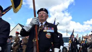 Ex-servicemen take part in a parade in Normandy to commemorate the D-Day landings