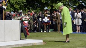 "Britain""s Queen Elizabeth lays a wreath during a bi-national France-UK D-Day commemoration ceremony at the British War Cemetery of Bayeux on June 6,"