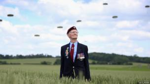 Fred Glover, aged 88, a veteran of the 9th Para Battalian watches a parachute jump just outside Rainville during D-Day 70 Commemorations on June 5, 2014 in Ranville, France.