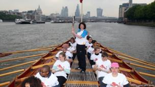 Baton bearer Rebecca Donnelly holds the Queens Baton on board the Gloriana as it makes its way down the River Thames