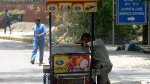 An ice cream vendor takes a nap while leaning on his push cart in the city centre.