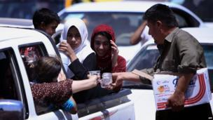 Iraqi families are given water as they gather at a checkpoint near Erbil, the autonomous Kurdistan region, on 10 June 2014.