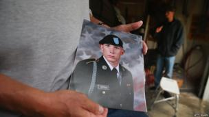 Jack Winter holds picture of nephew Aaron Toppen as family and friends grieve at Toppen's mother's home in Mokena, Illinois