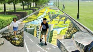 College students pose for pictures with a 3D painting along a street at a campus in Nanjing, Jiangsu province