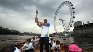 Baton-bearer Brian Dickens holds the Queen's Baton on board the Gloriana as it makes its way down the River Thames on 7 June 2014