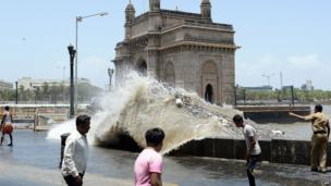 An Indian policeman (R) warns onlookers as waves come ashore during high tide near the Gateway of India in Mumbai on June 13, 2014. The Indian Meteorological Department (IMD) has declared the start of the monsoon season, predicting below-average rainfall.