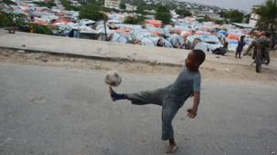 A boy playing football on a street in Mogadishu, Somalia - Thursday 12 June 2014