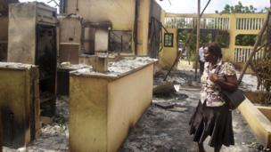 A woman observes the remains of the Breeze View Hotel, where residents watching the World Cup soccer tournament, were attacked and killed by militants, in the town of Mpeketoni,