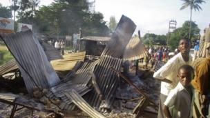 Residents observe the remains of roadside shops attacked by militants in the town of Mpeketoni,