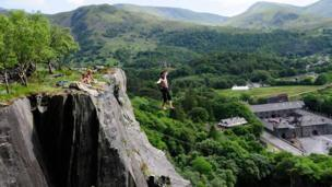 Slacklining over the void of the Vivian Quarry at Padarn Country Park, Llanberis