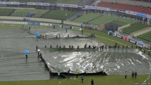 Groundsmen cover the field as rain stops play at the National Cricket Stadium in Dhaka.