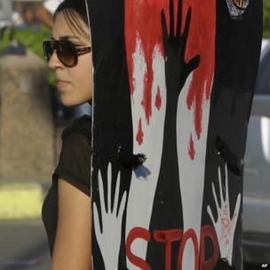 An Egyptian woman holds a banner against sexual harassment during a protest in Cairo, Egypt, Saturday, June 14, 2014