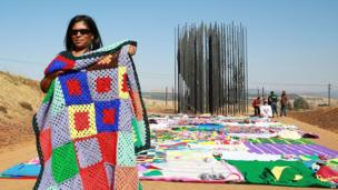 A woman prepares to lay a knitted blanket at the Nelson Mandela Capture Site in Howick, South Africa, on 15 June 2014