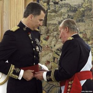 King Juan Carlos places the Sash of Captain-General on new King Felipe VI during a ceremony at La Zarzuela Palace in Madrid