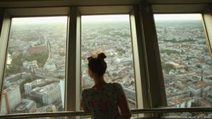 A young woman looks down at central Berlin from the broadcast tower at Alexanderplatz