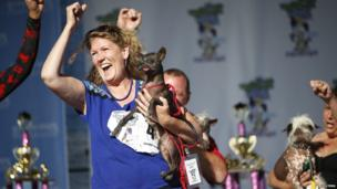 Katherine Kobliner celebrates after her dog Yoda, a Xoloitzcuintle, is placed third in the pedigree category.