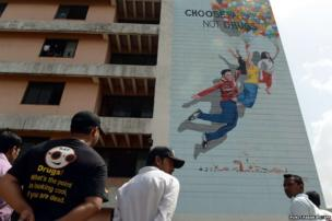 People look up at a newly-painted mural in Mumbai