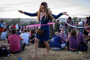 A festival goer uses a hula hoop at Glastonbury