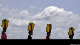 Women with carrying cartons of water on their heads, Mingkaman, Lakes State, South Sudan