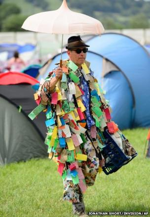 A man passes through Glastonbury music festival wearing a suit made from letters, England