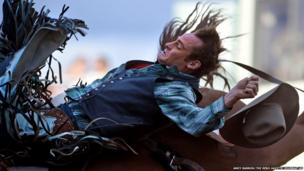 Kyle Brennecke loses his hat as he flies backwards during the bareback bronc riding event at the Reno Rodeo in Nevada