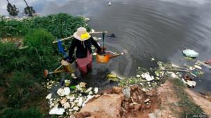 A woman carries water to spray onto vegetable plants in Samroang Tiev on the outskirts of Phnom Penh, Cambodia