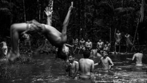 Villagers and players bathe in the local river