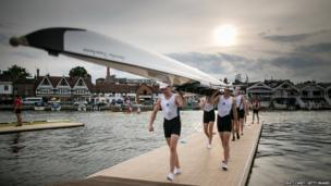A boat crew carries their boat from the river back to the boat tent at the end of the day's racing at the Henley Royal Regatta